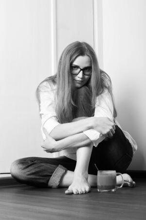 young woman at quarantine sitting on floor with mug of tea looks at camera, monochrome 版權商用圖片