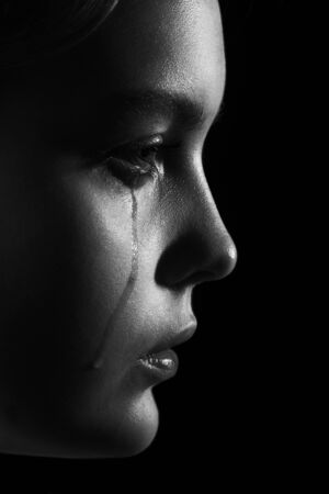 sad woman crying, looking aside on black background, closeup portrait, profile view, monochrome Stock Photo