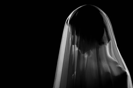 woman under white veil posing sensually on black background with copy space, profile side view monochrome