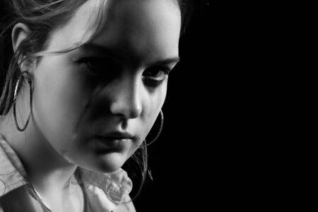 sad woman crying, looking at camera on black background, closeup portrait, monochrome Stockfoto