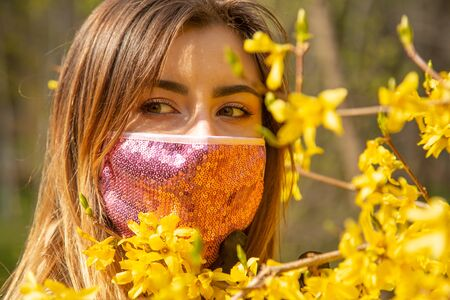 serious young woman with black medical protective mask at spring flowers looks at camera