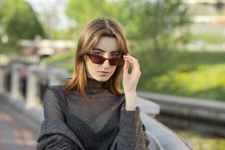 beautiful serious luxury young woman in sunny autumn park looks at camera over sunglasses 版權商用圖片