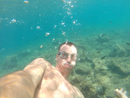 sports young man swims underwater in tropical sea makes selfie