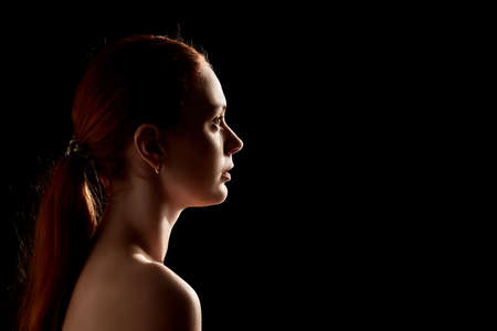 profile of young pensive woman on black background with copy space 免版税图像