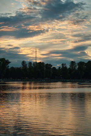beautiful sunset with golden clouds over city pond