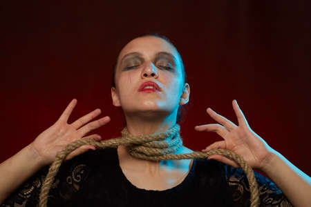 serious woman with rope on her neck on red background