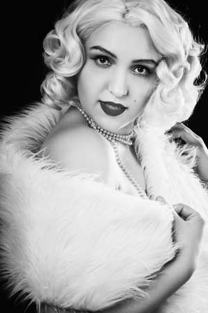 young luxury blond woman with white fur on black background, monochrome