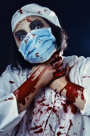 gloomy bloody woman doctor on a black background looking at camera