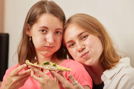 two women eats pizza looks at camera, smiling
