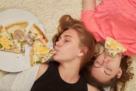 fun happy overeat girls lying with pizza pieces in mouth Reklamní fotografie