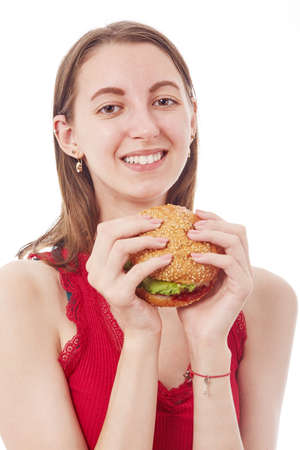 happy young woman show cheeseburger on white background isolated, looking at camera smiling Reklamní fotografie