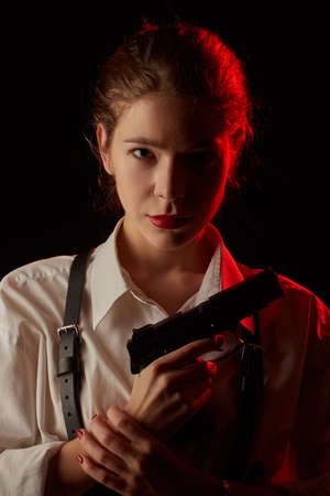serious young woman with gun in dark looking at camera toned image