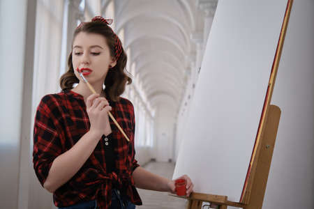 young pretty woman artist with brush near clean easel looking aside, thinking