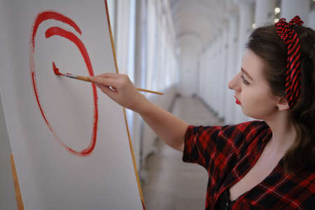 young pretty woman artist with brush near easel draws picture