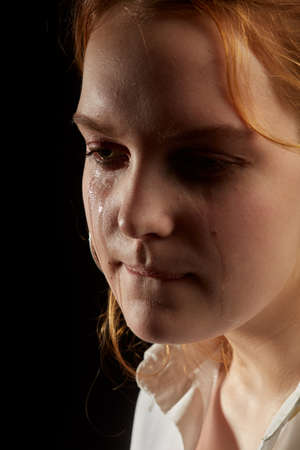 sad woman crying, looking aside on black background, closeup portrait