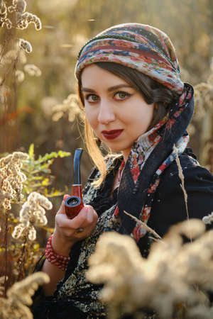 A young gypsy woman smoking pipe in autumn dry grass