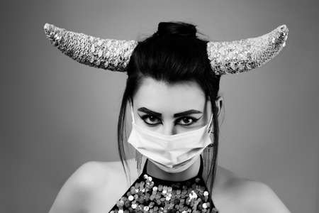 Taurus Zodiac Sign. Astrology and horoscope concept, Beautiful woman with medical mask, horns and creative makeup, monochrome