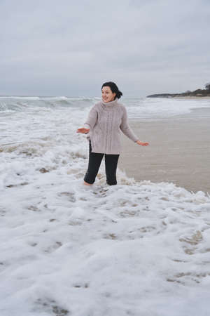 happy young woman on the shore of the cold winter sea