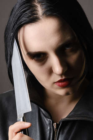 serious young woman with knife looking at camera closeup portrait Stock Photo