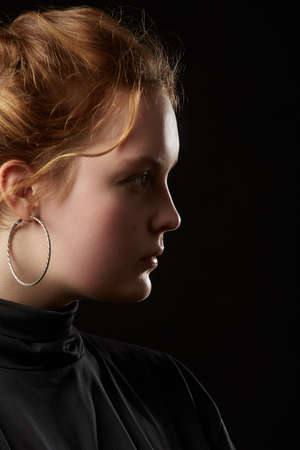 serious sad young woman with down syndrome on black background side profile view
