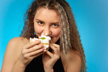 fun pretty curly blond hair girl with sweet dessert on cyan background Stock Photo