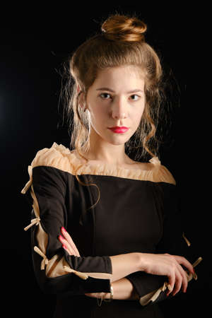 serious luxury young woman in black gothic dress on dark background looking at camera
