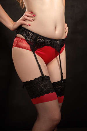 fat female body in red lingerie, stockings and belt closeup on black background