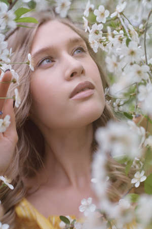 beautiful blonde woman near cherry blossoms close up portrait