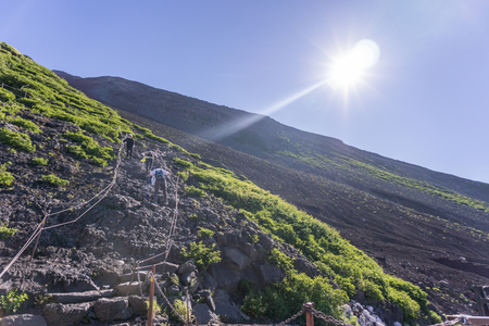 frontier: Mount Fuji, Japan. Hikers ascending Mount Fuji on a clear summer day.