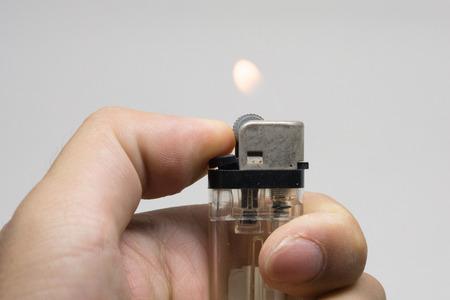 encendedores: La mano masculina que sostiene una encendedores de color blanco sobre fondo blanco, la mano con un encendedor