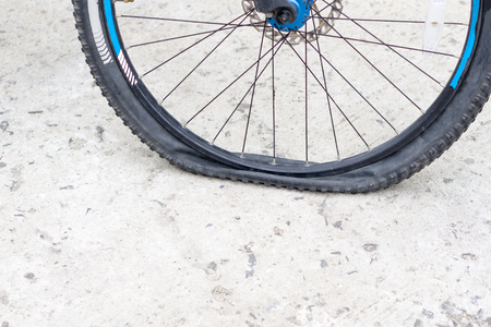 Closeup view of bicycle flat tire on pavement.