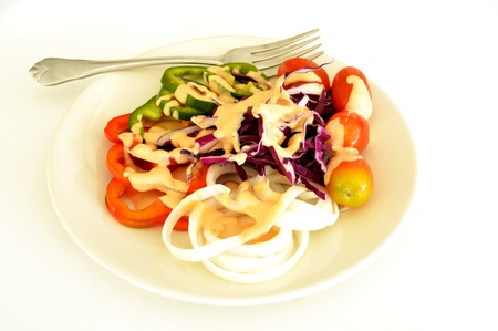 vegetable salad in white plate topped with thousand island dressing Stock Photo
