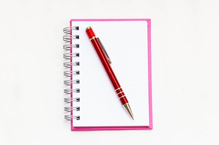 pink notebook with red pen on white background