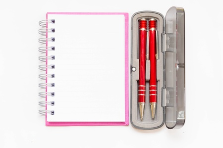 pink notebook with two red pen in box on white background