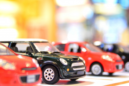 die: classic mini model car with red modern car on bokeh background Stock Photo