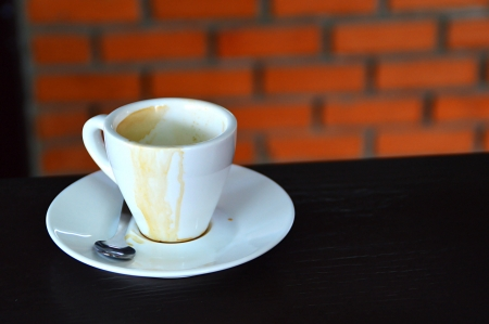 white cup of coffee on wooden table and brick background