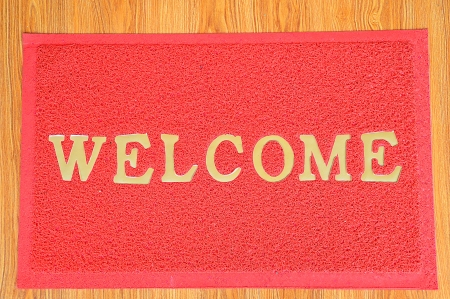 red welcome carpet on wooden background infront of office Stock Photo