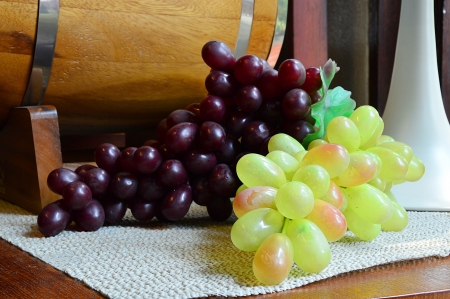 ripe grapes and green grapes on wooden table with wine barrel background photo