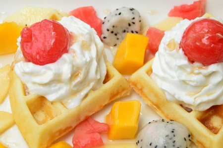 waffles with fresh fruits and cream on white plate