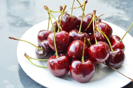 fresh cherries with water drops in white plate