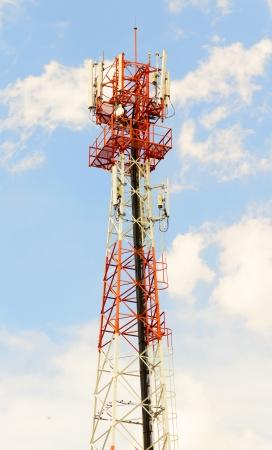 cielo despejado: roja y blanca torre de comunicaciones o del móvil con una gran cantidad de antenas bajo el cielo claro