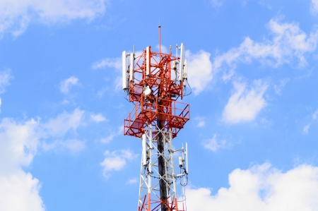 steel frame: Red and white tower of communications or mobilephone with a lot of different antennas under clear sky
