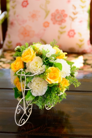 beatiful plastic bouquet of flowers on wooden table in coffee shop Stock Photo
