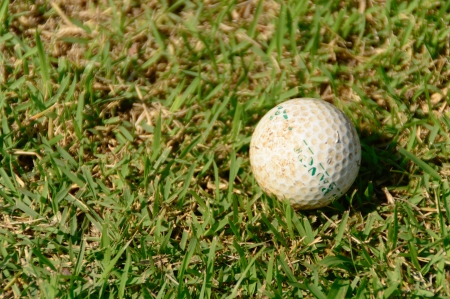 old golf ball on course with sunlight