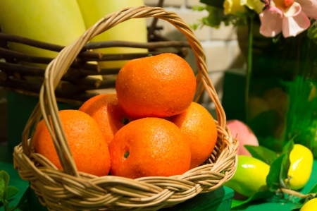 still life of plastic tangerines and basket
