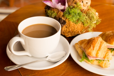 morning breakfast - coffee and croissant sandwish on restaurant table