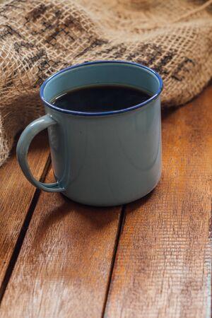 enamel mug on wood and sack bag background
