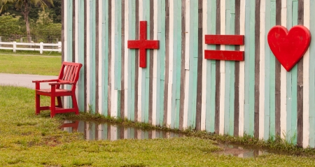 Wood red bench  in front of multi colour wall and symbol for lovers use for fun  photo