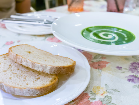 Spinash cream soup and  two breads ready to eat photo