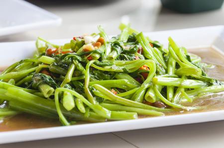 negocios comida: Sofrito de agua Spinachon plato blanco, comida tailandesa
